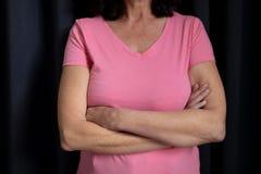 de vrouwen in roze voor borstkanker concentreren zich op gekruiste wapens Stock Afbeelding