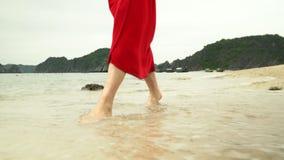 De vrouwen` s benen sluiten omhoog De oceaan op een achtergrond De vrouw in een rode kleding loopt op het strand Close-up van moo stock videobeelden