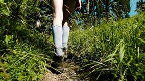 De vrouwen` s benen in trekkingslaarzen en golfschoenen gaan en Idt langs de weg in het bos tussen wildflowers in een stijging ui stock video