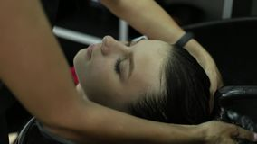 De vrouwen` s haar van kapperwassen in de schoonheidsstudio stock video
