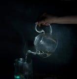De vrouwen` s hand giet kokend water in een glasketel Donkere achtergrond wijnoogst Royalty-vrije Stock Afbeelding