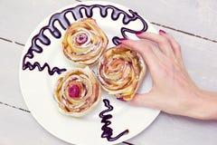 De vrouwen` s hand neemt één van drie appelmuffins royalty-vrije stock afbeeldingen