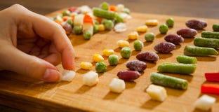 De vrouwen` s hand verzamelt zelfs rij van kleurrijke Bevroren gemengde groenten op een houten achtergrond Stock Foto's