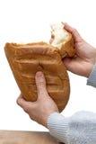 De vrouwen` s handen breken een stuk van brood af stock foto