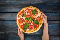 De vrouwen` s handen die een perfecte pizza Margarita met tomatenplakken, olijven en basilicum houden gaat weg Hoogste mening Stock Foto's