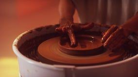 De vrouwen` s handen op pottenbakkers` s wiel vormen de kleine bodem van de kleiplaat stock footage