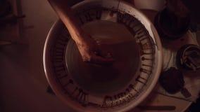 De vrouwen` s handen werken aan pottenbakkers` s wiel vormend lange dunne kleipot stock video