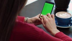 De vrouwen` s Handen zoeken Informatie in de Telefoon met het Groen Scherm stock videobeelden