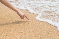 De vrouwen` s vinger trekt op strandzand royalty-vrije stock fotografie