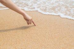 De vrouwen` s vinger trekt op strandzand stock foto