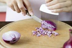 De vrouwen snijden rode ui met een speciaal apparaat Royalty-vrije Stock Foto