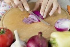 De vrouwen snijden rode ui op houten raad Stock Foto's