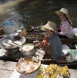 De vrouwen van Damnoensaduak treffen weghalen voedsel bij de het drijven markt Thailand voorbereidingen Stock Fotografie