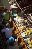 De vrouwen van Damnoensaduak treffen weghalen voedsel bij de het drijven markt Thailand voorbereidingen Stock Afbeelding