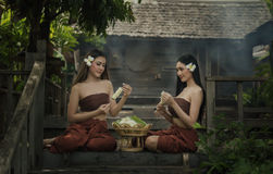 De vrouwen van Thailand in traditionele kledingszitting voor gemaakt van bloemslingers Royalty-vrije Stock Afbeelding