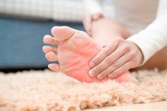 De vrouwen van de de verwondingspijn van de voetenkel raken haar pijnlijke voet, gezondheidszorg en geneeskundeconcept royalty-vrije stock fotografie