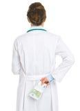 De vrouwen verbergend pak van de arts euro achter rug Stock Afbeelding