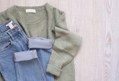 De vrouwen vormen kleren op houten achtergrond Vlak leg gestileerd wijfje kijken Sweater en jeans Hoogste mening Het winkelen con stock afbeelding