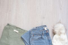De vrouwen vormen kleren op houten achtergrond Vlak leg gestileerd wijfje kijken Sweater, jeans en bonthoed Hoogste mening Het wi stock afbeelding