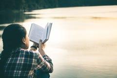 De vrouwen in de winter zitten gelezen favoriet boek in de vakantie stock afbeelding