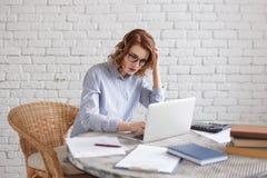 De vrouwen wordt beklemtoond bij het werk in het bureau De bedrijfsvrouw zeer ernstig voor haar laptop in het bureau royalty-vrije stock foto's