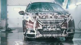 De vrouwenarbeider in garage de automobiele dienst een auto in het zeepsop door waterslangen wast, sluit omhoog