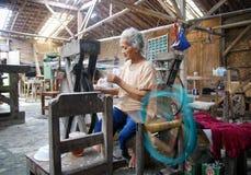 De vrouwenarbeider weeft stof in een wevende fabriek stock fotografie