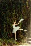 De vrouwenballerina in een witte kleding danst elegant Stock Afbeelding