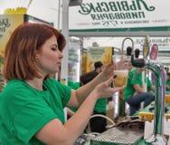 De vrouwenbarman giet Lvivske-bier openlucht in Kiev, de Oekraïne royalty-vrije stock fotografie