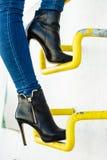 De vrouwenbenen in denimbroek hielt schoenen openlucht royalty-vrije stock foto