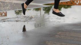 De vrouwenbenen lopen en springen in vulklei, waterplons stock videobeelden