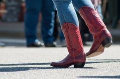 De vrouwenbenen met rode Amerikaanse laarzen bij land tonen binnen stock fotografie