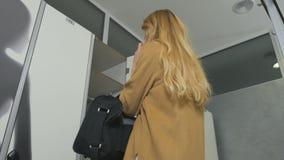 De vrouwenbesprekingen op telefoon komt aan de kleedkamer met sportieve zak stock videobeelden