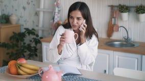 De vrouwenbesprekingen op telefoon, maakt nota's in agenda, drinkt thee op keuken, langzame motie stock video
