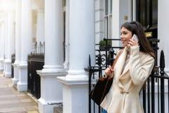 De vrouwenbesprekingen van Londen op haar voor traditionele Victoriaanse Huizen stock foto
