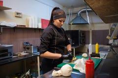 De vrouwenchef-kok bereidt verse sushi in de keuken van het restaurant voor stock foto's