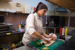 De vrouwenchef-kok bereidt verse sushi in de keuken van het restaurant voor stock foto