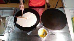 De vrouwenchef-kok kookt een pannekoek in keuken op professioneel rooster tijdens gebraden gerecht Het proces om pannekoeken op p stock videobeelden