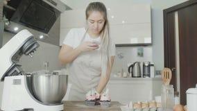 De vrouwenchef-kok maakt foto van haar cupcake aan instagram stock videobeelden