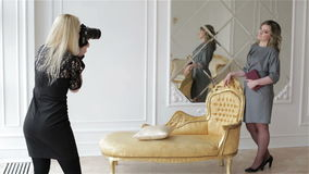 De vrouwenfotograaf in zwarte kleding werkt met meisjesmodel in grijze kleding stock footage