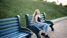 De vrouwengangen in het park onderzoekt smartphone vindt het ongemak van haar voeteneinden op bank gaat zitten stock videobeelden