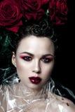 De vrouwengezicht van de schoonheidsmannequin Portret met rode roze bloemen Rode lippen en spijkers Mooie Donkerbruine Vrouw met  Stock Foto