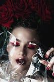 De vrouwengezicht van de schoonheidsmannequin Portret met rode roze bloemen Rode lippen en spijkers Mooie Donkerbruine Vrouw met  Royalty-vrije Stock Afbeeldingen