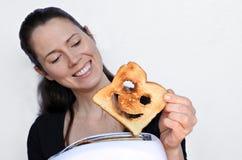 De vrouwenglimlach en houdt een goede plak van toost Stock Afbeeldingen