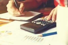 De vrouwenhand berekent over uitgaven en het maken van nota over lijst bij Stock Foto's
