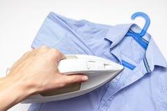 De vrouwenhand die een modern elektro wit ijzer, een blauw overhemd op achtergrond houden, sluit omhoog mening - het strijken, wa stock afbeelding