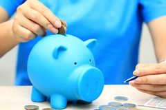 De vrouwenhand die een muntstuk zetten in spaarvarken op natuurlijke groene achtergrond, handelsinvesteringen en bespaart geld vo royalty-vrije stock afbeeldingen