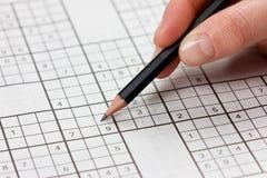 De vrouwenhand die een potlood houden en lost kruiswoordraadselsudoku op Stock Afbeeldingen