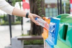 De vrouwenhand die van het close-upportret lege plastic waterfles in het recycling van bak werpen stock foto