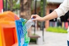De vrouwenhand die van het close-upportret lege plastic waterfles in het recycling van bak werpen stock afbeeldingen